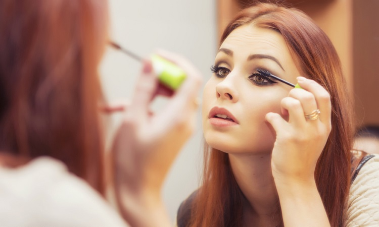 stock-photo-brunette-woman-applying-make-up-paint-her-eyelashes-for-a-evening-date-in-front-of-a-mirror-357502742