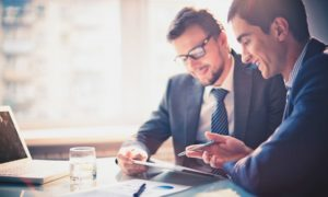 stock-photo-image-of-two-young-businessmen-using-touchpad-at-meeting-158522279