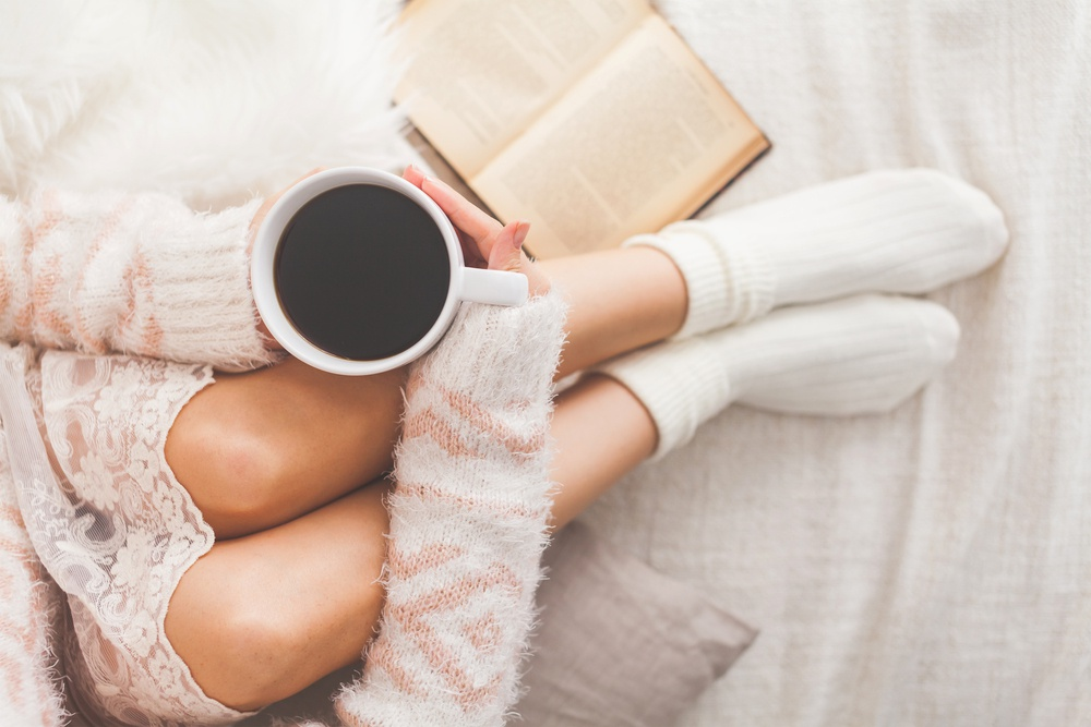 soft-photo-of-woman-on-the-bed-with-old-book-and-cup-of-coffee-in-hands-top-view-point