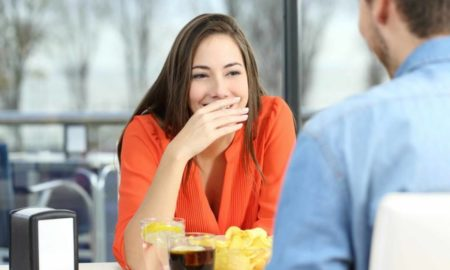 stock-photo-woman-covering-her-mouth-to-hide-smile-or-bad-breath-during-a-date-in-a-coffee-shop-with-a-window-360886088