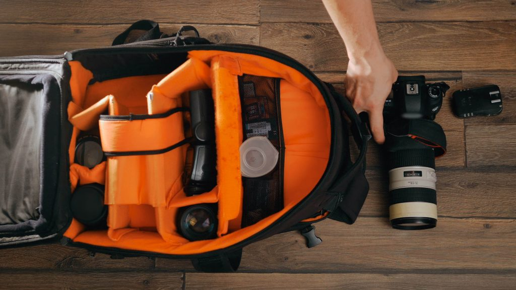 stock-photo-photographe-pack-his-camera-and-lenses-to-bagpack-bag-appliances-for-photography-top-view-530790337