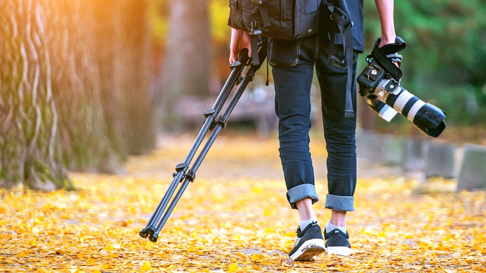 stock-photo-professional-photographer-with-camera-and-tripod-in-autumn-517236289
